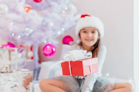 Blurred smiling santa child sitting under fir-tree, extending a gift wrapped for Christmas to the camera. Focus on the red box.
