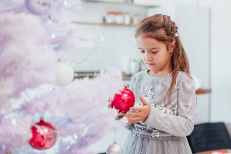 Cute girl is looking at one of pink balls on the christmas tree, with thoughtful face expression.