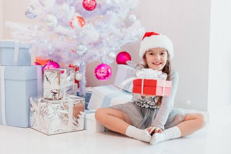 Smiling santa child sitting under fir-tree, extending a gift wrapped for Christmas to the camera. Stok Fotoğraf