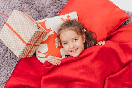 Sweet little kid woke up in the morning with Christmas gift on her side.