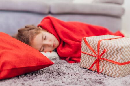 Angelic daughter is sleeping on the carpet, covered with red blanket, with Christmas gift on her side. Stok Fotoğraf