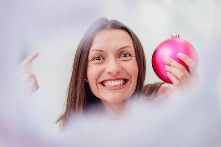 Closeup of young woman holding a pink bauble for the Christmas tree, showing off what nice toys she has bought for this christmas. Stok Fotoğraf