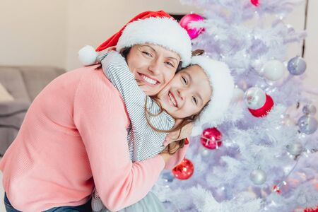 Loving mother and daughter hugging near christmas tree, looking amazing. Stok Fotoğraf