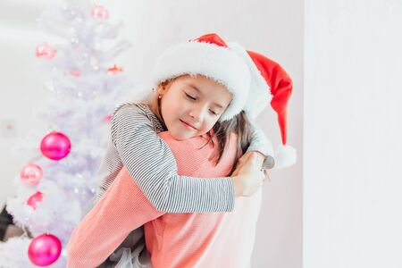 Lovely mom and daughter managed to decorate a fir-tree and are hugging, satisfied with a good job together. Stok Fotoğraf