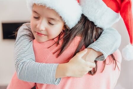 Cropped shot of loving mother and daughter hugging near christmas tree, looking amazing.