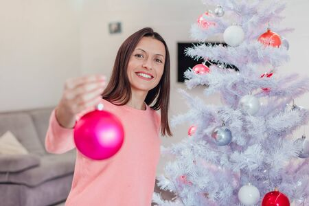 Young woman in a pink sweater holding a Christmas decoration bauble for the Christmas tree, showing off what nice toys she has bought for this christmas.