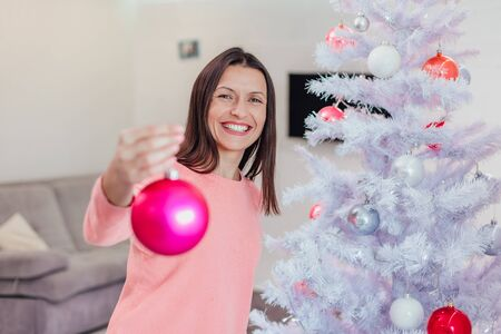 Beautiful businesswoman is decorating new year tree with pink glass baubles, looking pleased with the process.