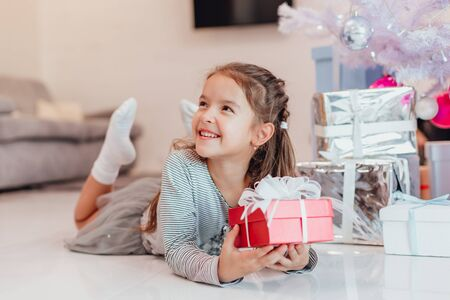 Beautiful little angel girl with perfect smile laying on the floor, holding a red present box with white bow. Stok Fotoğraf