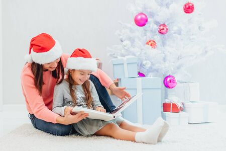 Sweet mother and daughter are looking through the family photo album, recollecting their good old memories on Christmas Eve.