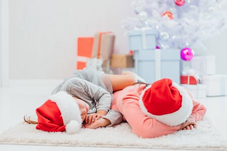 Two exhausted females, mother and daughter, are sleeping side by side after new year party.