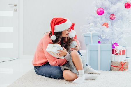 Image of caring mum giving present her daughter while sitting on the carpet near christmas tree in new year time.