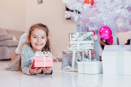 Careless, smiling small female enjoying Christmas time and presents. Stok Fotoğraf