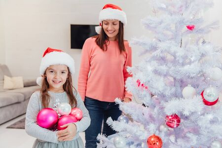 Mother and daughter relationships concept. Happy mother and her little daughter decorate a fir-tree together on Christmas Eve.