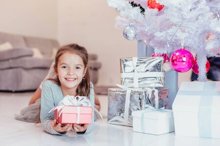 Beautiful little angel girl with perfect smile laying on the floor, holding a red present box with white bow. Stock fotó