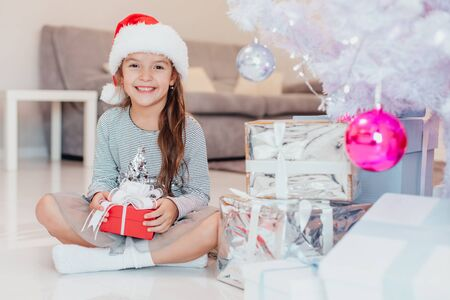 Light photo of cute kid sitting with gift in hands, like a little gnome in christmas decorated room. Stok Fotoğraf