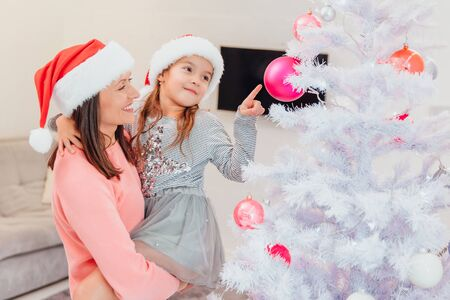 Mother holds her daughter, standing near christmas tree, cute girl is pointing at one of pink baubles on the fir branch.
