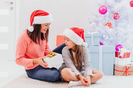 Mother in santa hat is going to give her lovely daughter a present, daughter is looking at the box surprised, with month opened. Stok Fotoğraf
