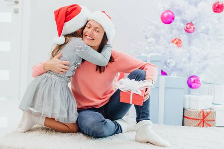 Caucasian mum and daughter are exchanging gifts on Christmas Eve.