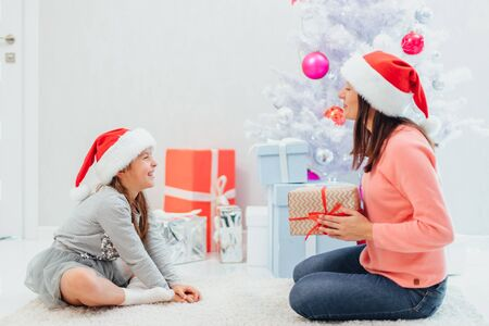 Cute inspired girl is waiting for her mum to give her a present. Stok Fotoğraf