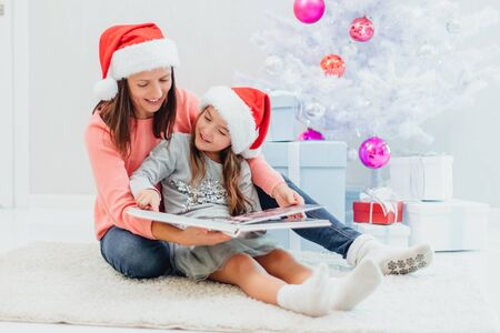 Pretty young mom reading an interesting book to her cute daughter near Christmas tree indoors. Stok Fotoğraf