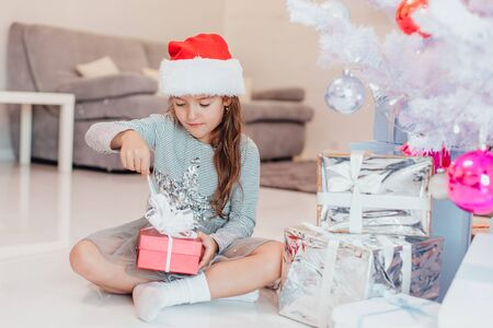 Full-body photo of super excited young girl opening a christmas present while sitting on the floor in lotos position. Stok Fotoğraf