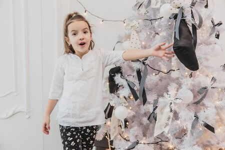 Excited little girl with open mouth pointing at the beautifully decorated christmas tree with lights, balls and socks. Banco de Imagens