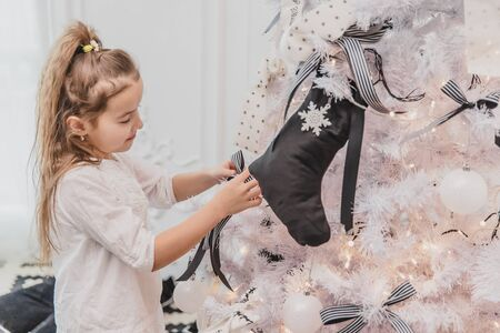 Small brunette girl is decorating a Christmas tree with colorful bows, socks and baubles at home. Banco de Imagens