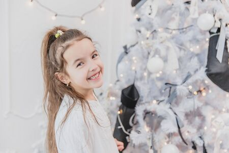 Close-up of smiling girl, little snow princess, near christmas tree, on a white background.