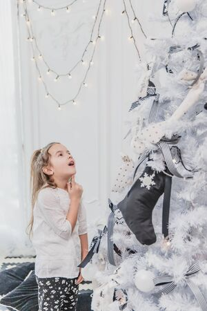 Little girl is totally fascinated by beautifully decorated christmas tree with lights, balls and socks.