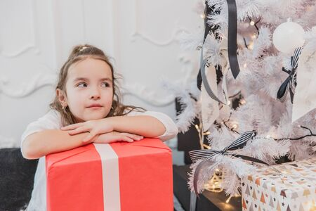 Careless, smiling small female enjoying Christmas time and presents. Banco de Imagens
