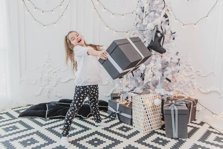 Pretty kid is happy and surprised to get the biggest gift for Christmas and now she is carrying this heavy box with white bow. Banco de Imagens