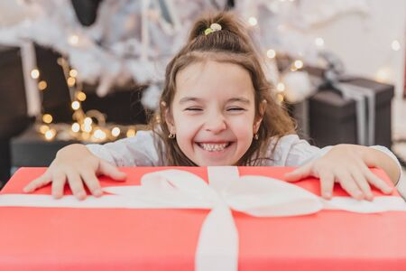 Closeup photo of super excited young girl opening large christmas present while sitting on living room floor. Banco de Imagens