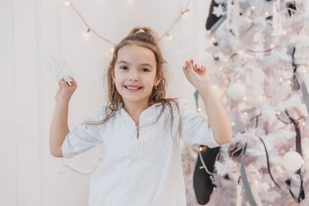 Small brunette girl is decorating a Christmas tree with silver snowflakes at home. Banco de Imagens