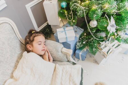 Angelic child daughter is sleeping on the sofa near Christmas tree with gifts. Banco de Imagens