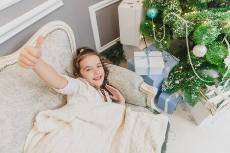 Inspired child daughter on the Christmas morning near Christmas tree with gifts. Banco de Imagens