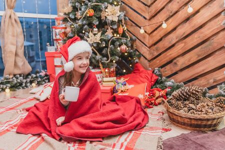 Beautiful child in santa hat, wrapped in red blanket near christmas tree, with a cup of cocoa, looking delighted and pleased. Banco de Imagens