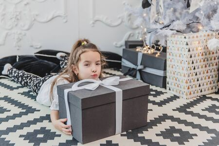 Sleepy child in christmas pajamas is laying on the floor under the christmas tree, keeping her chin on the large present. Banco de Imagens