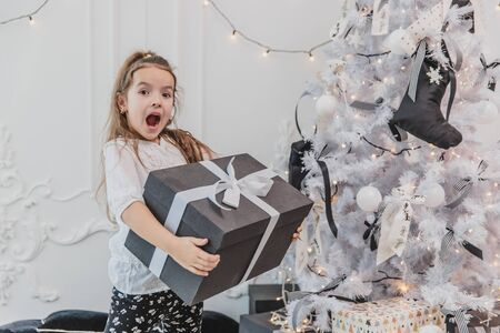 Pretty kid is happy and surprised to get the biggest gift for Christmas and now she is carrying this heavy box with white bow.