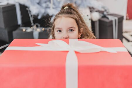 Closeup new year photo of a child looking from behind the giftbox with her eyes widened in amazement.