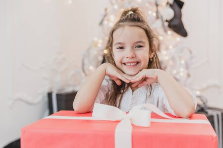 Pretty kid is happy and surprised to get the biggest giftbox with white bow for Christmas . Banco de Imagens