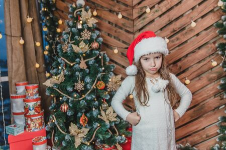 Disappointed little girl wearing Christmas costume standing isolated over wooden christmas background, keeping arms akimbo, frowning her face.