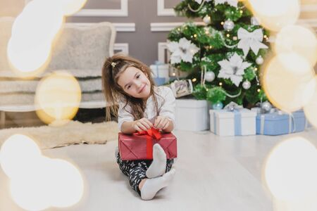 Light photo of cute kid sitting with gift in hands, like a little gnome in christmas decorated room. Banco de Imagens