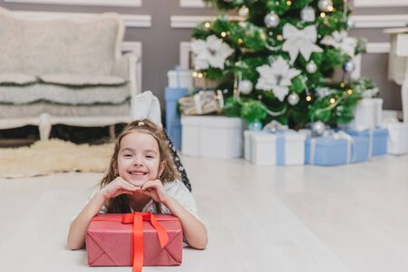 Closeup of beautiful little angel girl with perfect smile laying on the floor, keepin hands on big present box with ribbon. Banco de Imagens