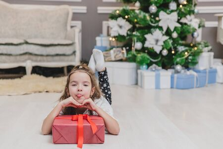 Closeup of beautiful little angel girl making grimaces, laying on the floor, keepin hands on big present box with ribbon.