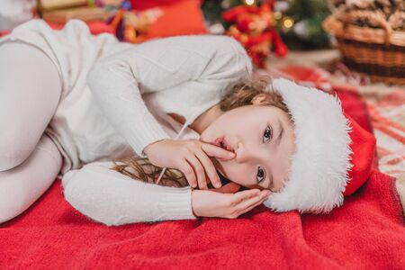 Close-up of lovely child is going to sleep and shows silence sound on red blanket near Christmas tree.