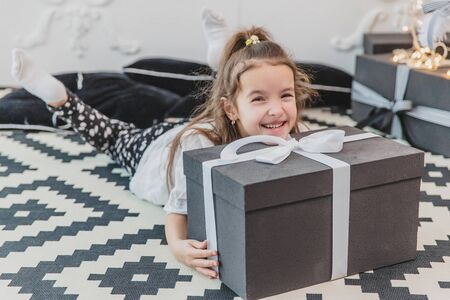 Sleepy but happy child in christmas pajamas is laying on the floor under the christmas tree, keeping her chin on the large present. Banco de Imagens - 133207982