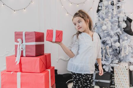 Lovely little girl playing with Christmas giftboxes, building a pyramid. Banco de Imagens