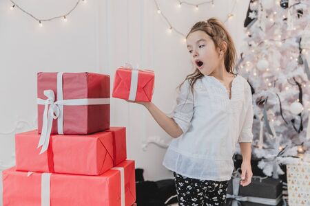 Lovely little girl playing with Christmas giftboxes, building a pyramid. Zdjęcie Seryjne