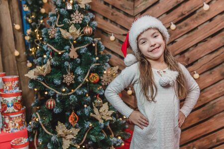Portrait of funny girl child in a red hat for Christmas under a decorated fir-tree on wooden background. Stock Photo