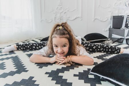 Cute little kid in splits position, leaning to the camera and smiling lovely, in white-black designed rooom.